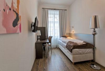 Jednolůžková postel v pokoj vlevo stůl s TV a židlí napravo stojací lampa