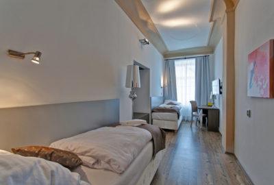Pokoj se dvěma postelemi jednolůžkovými naproti sobě. vpravo stůl se ždilí
