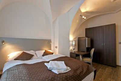 Dvoulůžková postel v pokoji na posteli ručníky na pravo skříň před skříní psací stůl