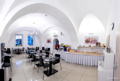 Místnost se stoly a židlemi vpravo pult s jídlem