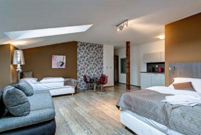 Podkrovní pokoj napravo manželská postel na levou gauč vlevo od gauče jednolůžková postel