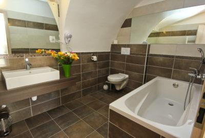 Koupelna s vanou napravo vlevo umyvadlo se zrcadlem
