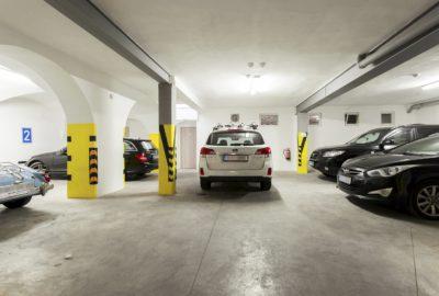 Garáž v hotelu vlevo dvě parkovací místa v pravo dvě parkovací místa uprostřed stojící auto