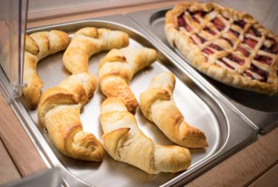 Detail pokrmu: domácí croissant a koláč