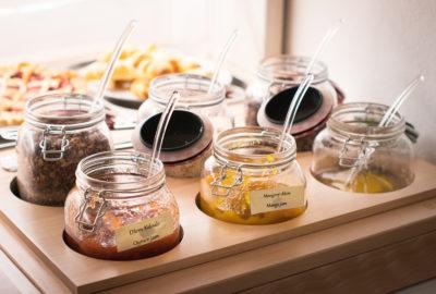 Marmelády v otevřených sklenicích se lžičkou