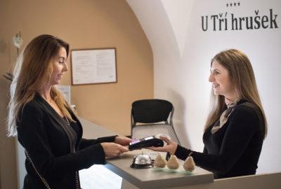 Host žena platí recepční kreditní kartou v hotelu na recepci