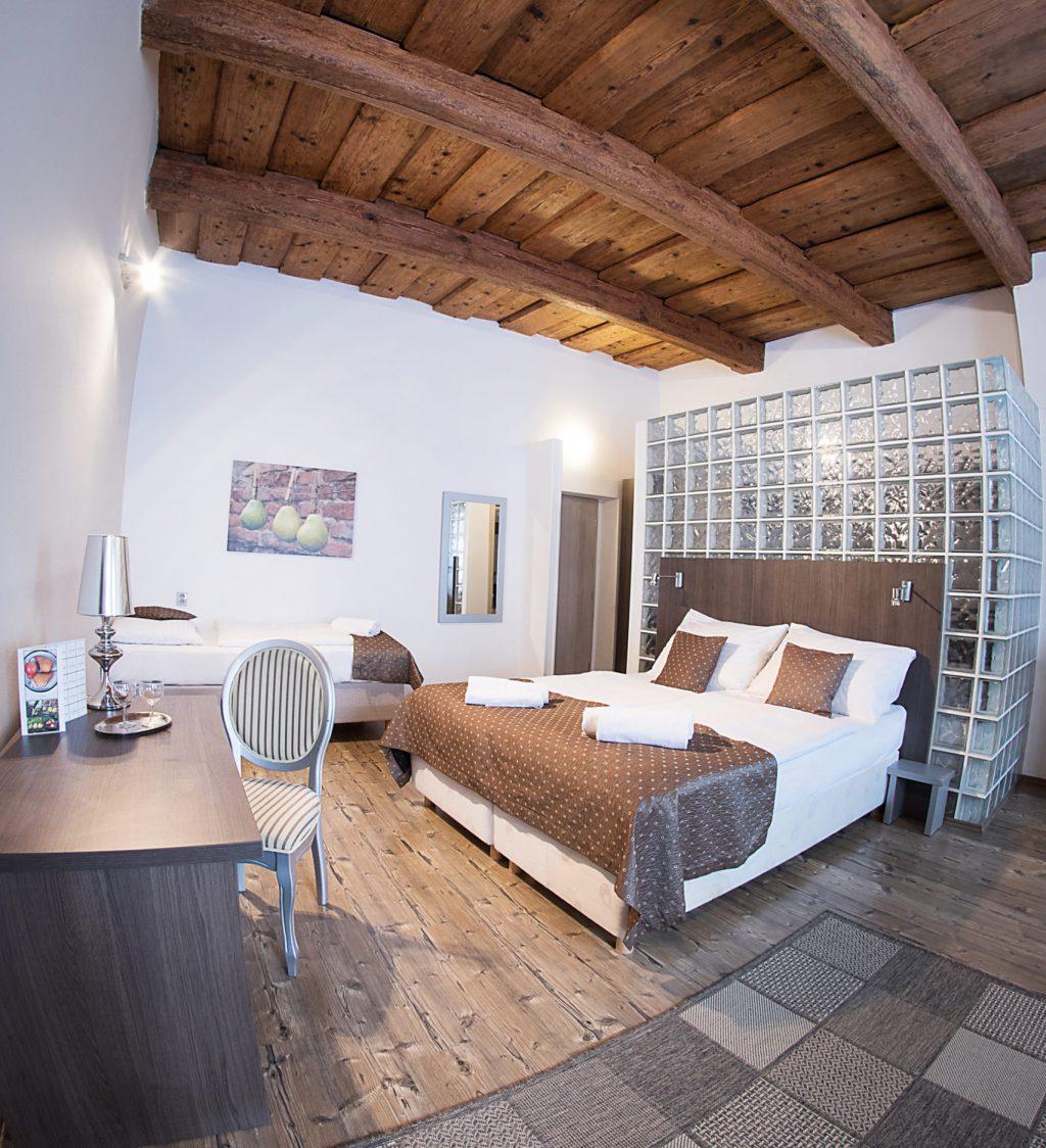 Pohled na postel v pokoji před postelí koberec vlevo psací stůl se židlí