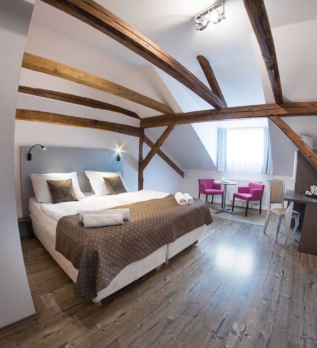 Manželská postel ve dvoulůžkovém pokoji na pravo koberec se stolem a dvěma křesly