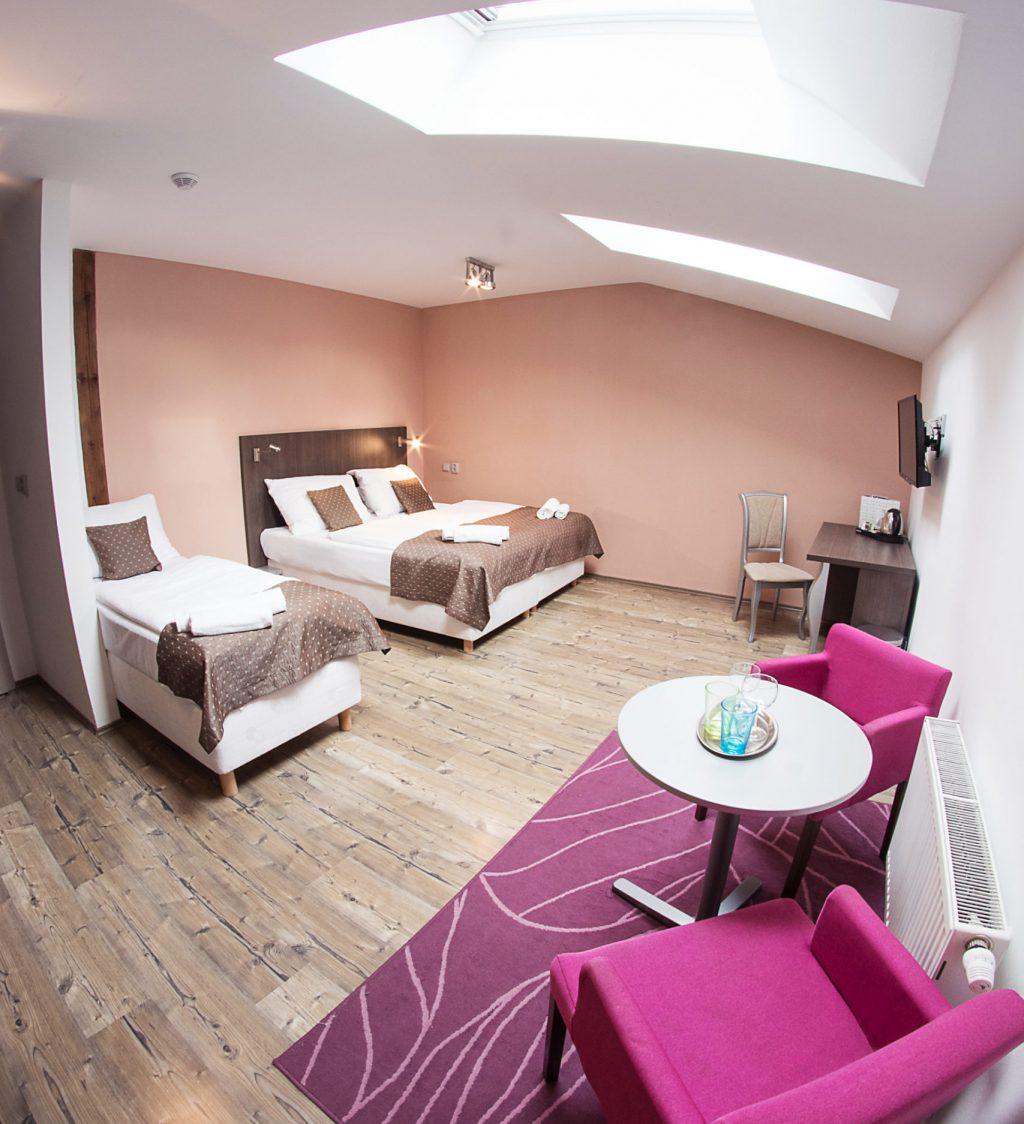 Pokoj se třemi postelemi, dvoulůžková a jednolůžková postel, vpravo koberec se stolem a dvěma křesly